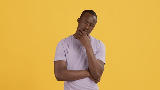 Black man thinking about problem solution, orange background