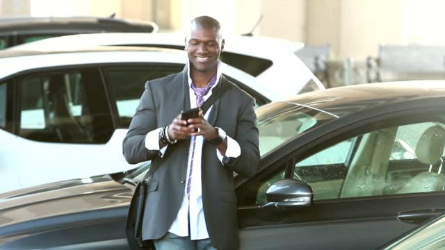 Black man walking thru parking lot looking at phone video