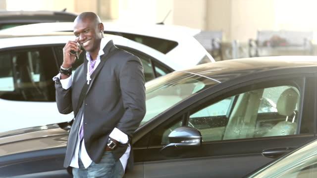 Black man walking thru parking lot talking on phone video