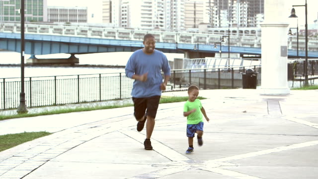 Black man with young son jogging in city park video