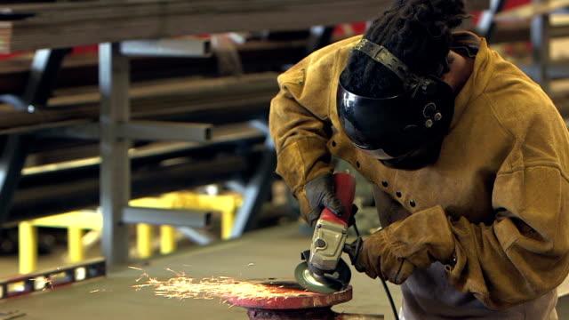 Black man working in factory, grinding metal pipe joint