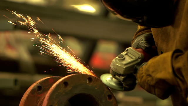 Black man working in factory, grinding metal pipe joint A young black man working in a factory, grinding a steel pipe. He is wearing a protective mask, clothing and gloves. metal worker stock videos & royalty-free footage