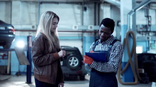 Black mechanic discussing a job sheet video