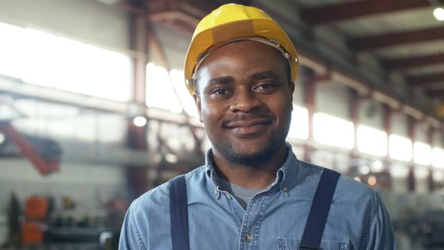 Black mechanic smiling at camera Pan close-up of Afro-American mechanic with relaxed happy smile standing in sprawling sunlit factory facility, wearing denim shirt and yellow hardhat satisfaction stock videos & royalty-free footage
