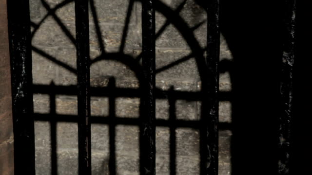 Black metal bars and old stone wall cell An unwelcoming entrance to an old stone schoolhouse, with metal bars and spikes on the gate, giving the effect of a prison cell rather than a school. Dolly shot moving right to left. human trafficking stock videos & royalty-free footage