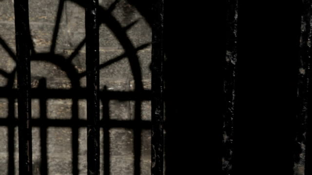 Black metal bars on a cold stone prison cell video