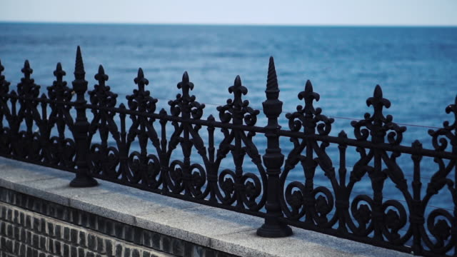 black metal fence on the background of water. decorative fence in the form of a balustrade. the camera moves along the fence. close up - balaustrata video stock e b–roll