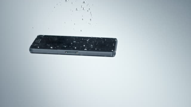 slo mo ld black mobile phone sinking into clear water and causing bubbles - погружённый стоковые видео и кадры b-roll