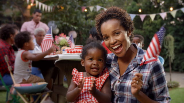 Black mother and baby girl wave flag at 4th July party video