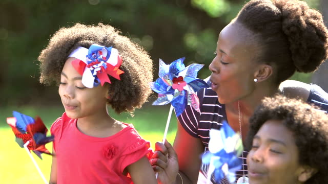 Black mother and children playing on American holiday An African-American woman and her two children having fun on the fourth of july or memorial day. They are playing with red, white and blue pinwheels. The little girl, 7 years old, has a patriotic bow in her hair. fourth of july videos stock videos & royalty-free footage