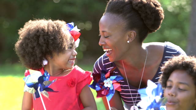 Black mother and children playing on American holiday An African-American woman and her two children having fun on the fourth of july or memorial day. They are playing with red, white and blue pinwheels. The little girl, 7 years old, has a patriotic bow in her hair. family 4th of july stock videos & royalty-free footage