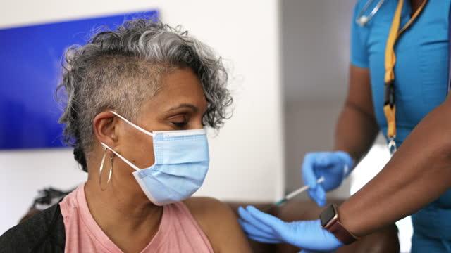 Black Nurse Giving Covid-19 Vaccine to Senior Black Woman A black nurse giving a Covid-19 Vaccine to a senior black woman vaccine stock videos & royalty-free footage