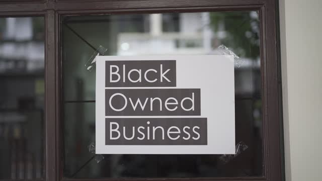 черный принадлежащий бизнес-знак, прикрепленный к окну - black history month стоковые видео и кадры b-roll