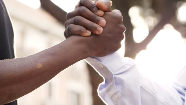 Black people friendship. hands shacking- slow motion
