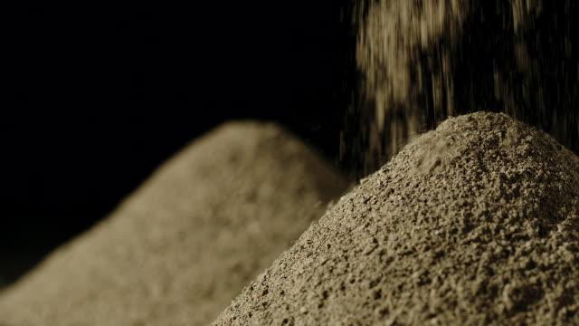 slow motion: schwarzes pfefferpulver in einem haufen gießen - gemahlen stock-videos und b-roll-filmmaterial