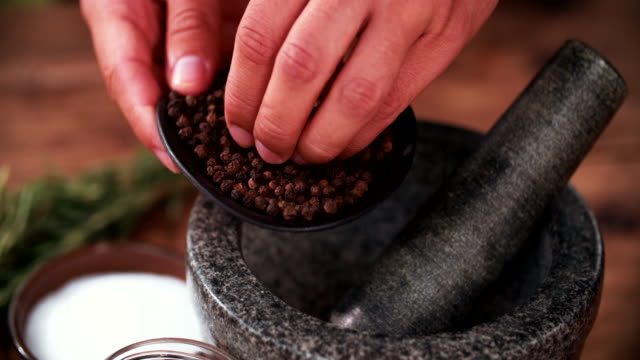 Black peppercorns being put into a mortar and pestle Person's hands putting black peppercorns into a dark stone mortar and pestle for crushing, with herbs and spices laid out on a wooden table in Slow Motion mortar and pestle stock videos & royalty-free footage