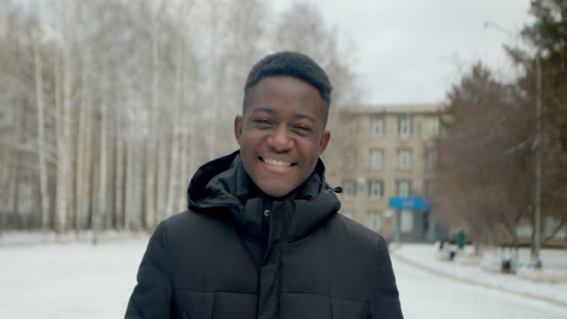Black portrait man face smile look at camera closeup american joy winter day 4K. video