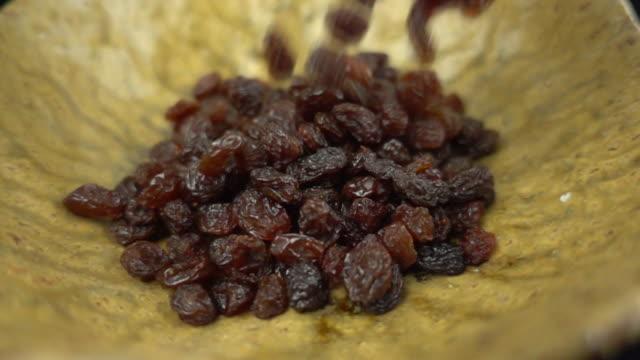 Black raisins falling in slow motion