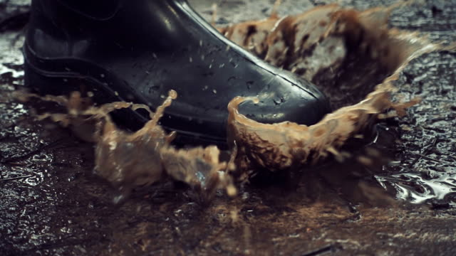 vídeos de stock e filmes b-roll de black rubber boots step on a puddle and creates a splash. slow mo, slo mo - bota