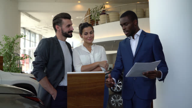 Black salesman showing a car properties to couple customer at a car dealership all smiling Friendly black salesman showing a car properties to couple customer at a car dealership all smiling car salesperson stock videos & royalty-free footage
