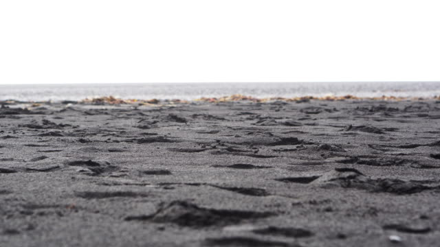4K Black sandy lava beach in Vik, Iceland. Low angle, tilt up landmark beach near basalt sea stacks video