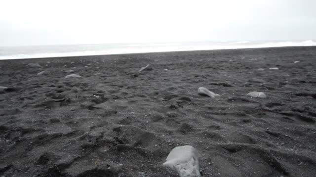black sandy lava beach in vik, iceland. slow motion 120fps low angle, tilt up landmark beach near basalt sea stacks - krajobraz morski filmów i materiałów b-roll