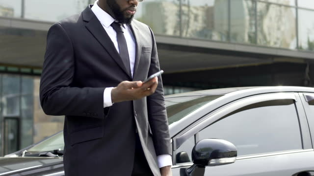Black security agent receiving important instructions from chief by phone Black security agent receiving important instructions from chief by phone security staff stock videos & royalty-free footage