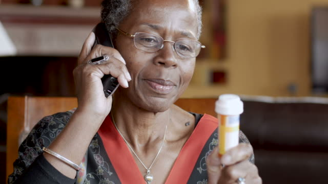 vídeos de stock e filmes b-roll de black senior woman refilling her prescription on a cordless landline phone - medicare