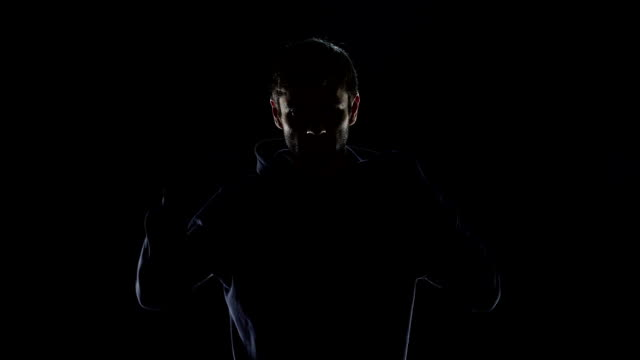 black silhouette of mysterious man wearing hood, intention to commit crime - mistero video stock e b–roll