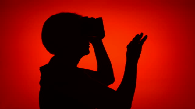black silhouette of senior woman using vr 360 glasses. female's face in profile on red background - ritratto 360 gradi video stock e b–roll