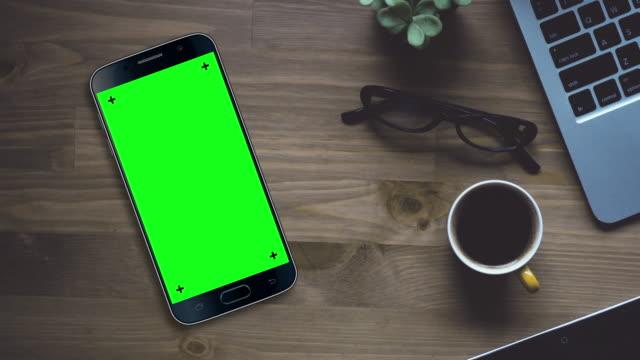black smartphone on desk with chroma key green screen - стол стоковые видео и кадры b-roll