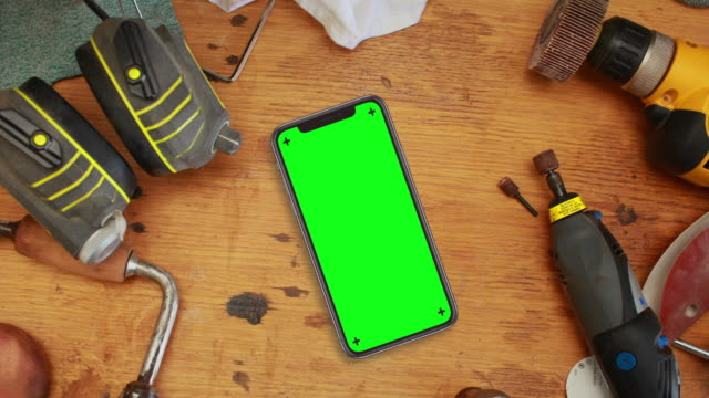 Black Smartphone on Workbench with Chroma Key Green Screen The camera slowly zooms in on a smartphone sitting a workbench surrounded by tools. Contains tracking markers on the phone's screen for easy tracking.  workbench stock videos & royalty-free footage
