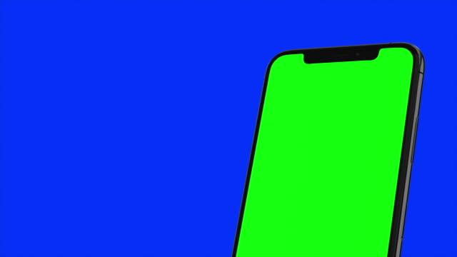 블랙 스마트 폰이 파란색 배경에 켜 집니다. 쉬운 사용자 정의 녹색 화면. 컴퓨터에서 생성 된 이미지입니다. - 스마트폰 스톡 비디오 및 b-롤 화면