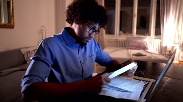 Black student studying at night to meet his deadline