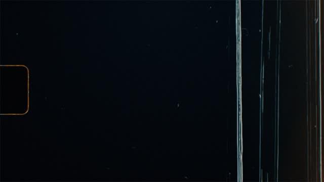 black super 8 film frame scan с отверстием для спрокетов, утечками света и абстрактным оранжевым текстом. для ретро винтажный вид. шум зерна и большие ца� - утечка света стоковые видео и кадры b-roll