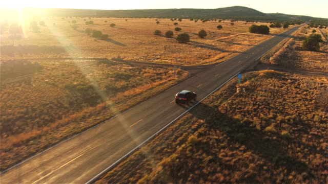 AERIAL: Black SUV car driving along empty country road at golden summer sunset