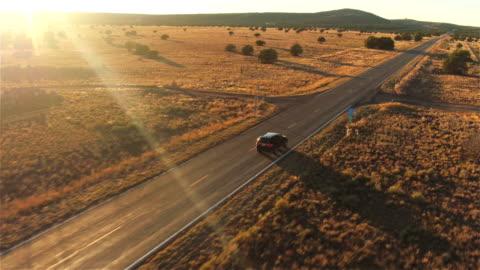 vídeos de stock e filmes b-roll de aérea : suv carro preto condução ao longo da estrada vazia país no verão sol dourado - cena rural