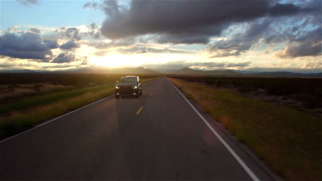AERIAL: Black SUV car driving along the empty countryside road at golden sunset video