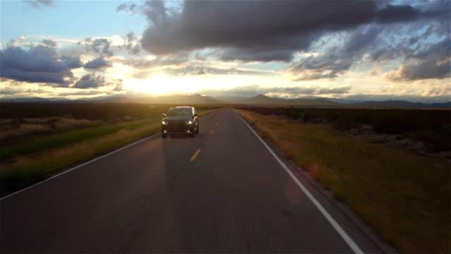 vídeos de stock, filmes e b-roll de vista aérea : preto utilitário carro dirigindo na estrada rural vazia na direção do pôr-do-sol - estrada principal estrada