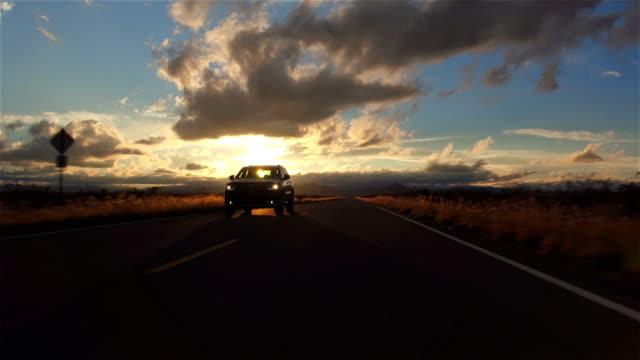 vídeos de stock, filmes e b-roll de vista aérea : preto utilitário carro dirigindo na estrada rural vazia na direção do pôr-do-sol - viagens rodoviárias