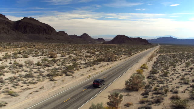 AERIAL: Black SUV car driving along the empty countryside road through desert video