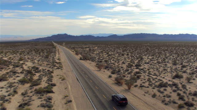 AERIAL: Black SUV car driving along the empty countryside road through desert AERIAL: Black SUV car driving along the picturesque empty road through the vast desert with big rocky mountains. People traveling, road trip through beautiful countryside scenery in sunny summer mojave desert stock videos & royalty-free footage