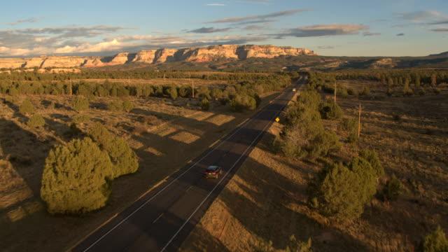 antenne schwarz suv auto fahren entlang der leeren straße in richtung mesa berge in utah - südwesten stock-videos und b-roll-filmmaterial