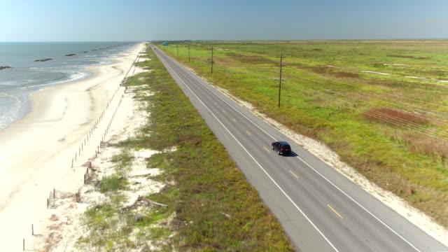 antenn: svart suv bil körning på landsbygden vägen längs den bay av mexiko - kustlinje bildbanksvideor och videomaterial från bakom kulisserna
