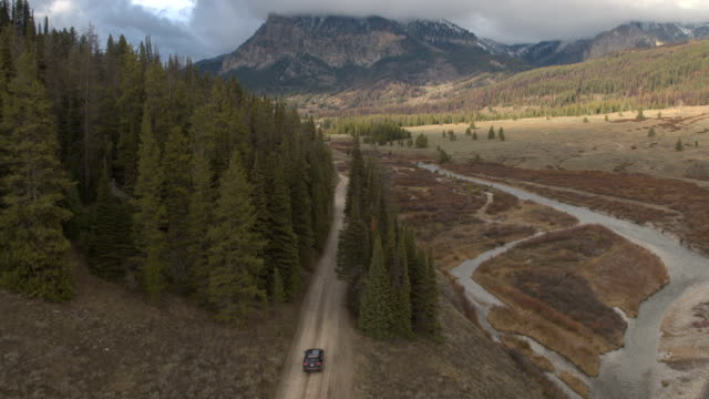 aerial black suv car driving on road trough river valley towards rocky mountains - ghiaia video stock e b–roll