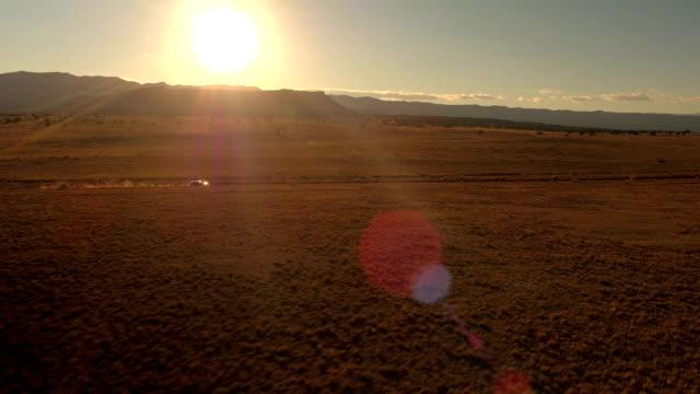 aerial: black suv car traveling on dusty road in desert valley at golden sunrise - дикая местность стоковые видео и кадры b-roll
