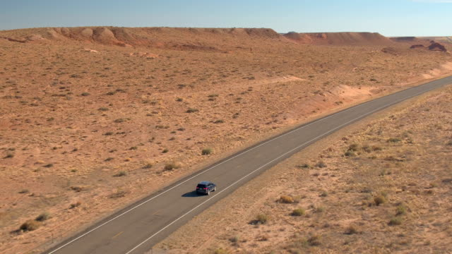 aerial: black suv jeep driving along the straight empty road through dry desert - дикая местность стоковые видео и кадры b-roll