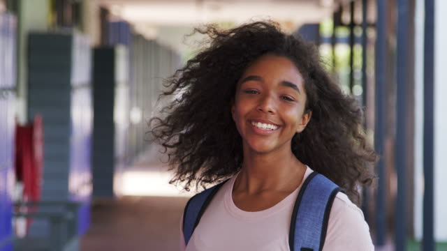 Black teenage girl walks into focus in high school corridor video