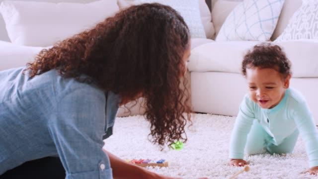 Black toddler boy crawling around his kneeling young mother Black toddler boy crawling around his kneeling young mother crawling stock videos & royalty-free footage