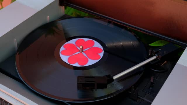 disco in vinile nero con cuori rossi che girano sul giradischi dj.  record player antiquario. needle suona album discografico equipaggiamento musicale popolare per anni '60, '70, '80, '90. concetto d'amore da vicino, macro - disco audio analogico video stock e b–roll